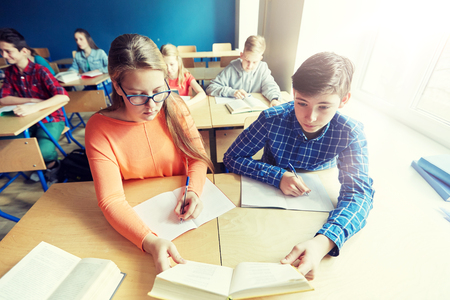 students reading book at school lesson