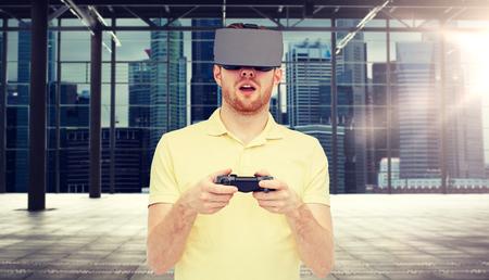 man in virtual reality headset with gamepad Standard-Bild
