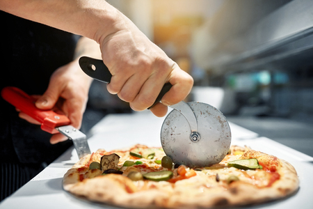 cook cutting pizza to pieces at pizzeria