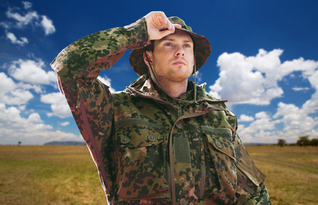 soldier or traveler in military uniform over sky Stock Photo
