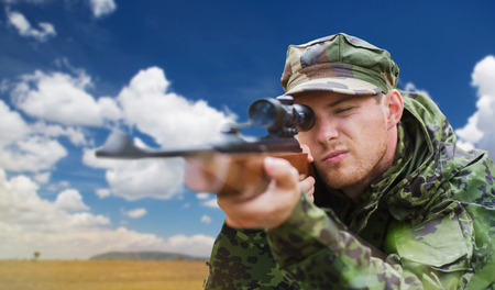 soldier or hunter with gun aiming or shooting