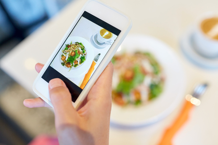 hand with smartphone photographing restaurant food