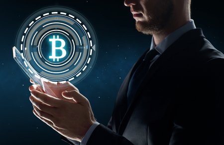 businessman with tablet pc and bitcoin hologram Zdjęcie Seryjne