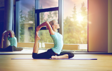 smiling woman stretching on mat in gym Banco de Imagens