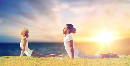 couple making yoga cobra pose outdoors