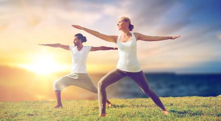 couple making yoga warrior pose outdoors