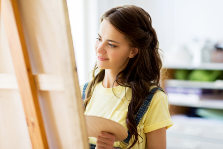 student girl with easel painting at art school Foto de archivo - 97896135