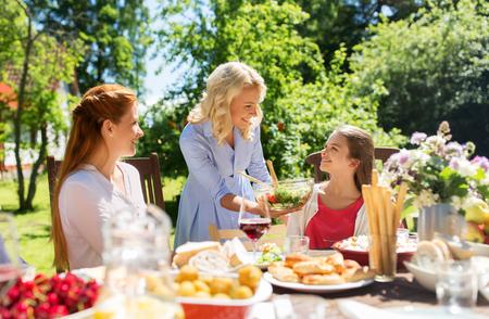 happy family having dinner at summer garden