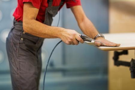 worker with glue gun and board at workshop Reklamní fotografie - 97896553