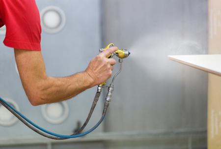 worker hand sprays urethane finish to board