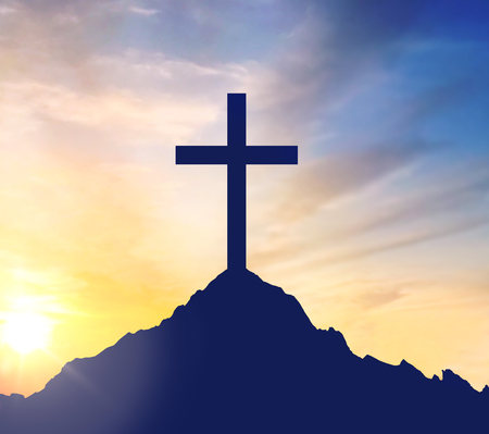 silhouette of cross on calvary hill over sky Stock Photo