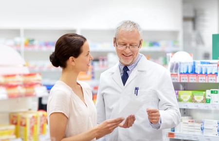 apothecary and woman with prescription at pharmacy Stock Photo