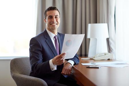 Geschäftsmann mit Papieren arbeiten im Hotelzimmer Standard-Bild - 98081413