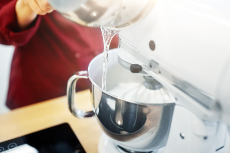 chef pouring ingredient from pot into mixer bowl