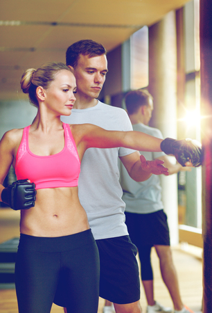 smiling woman with personal trainer boxing in gym