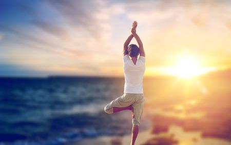 happy man making yoga tree pose over sea