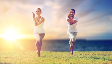 couple making yoga eagle pose outdoors