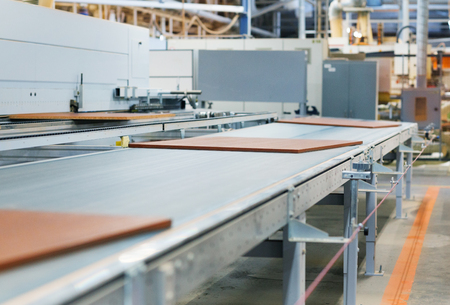 chipboards on conveyer at furniture factory