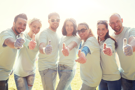 group of volunteers showing thumbs up outdoors Imagens