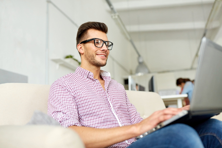 smiling man with laptop working at office