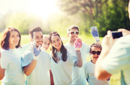 group of volunteers taking picture by smartphone Stock Photo