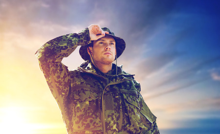 young soldier in military uniform over sky