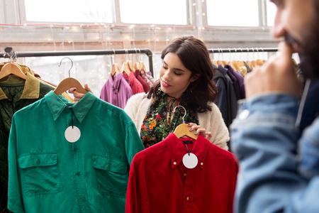 couple choisir des vêtements au magasin de vêtements vintage
