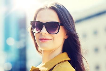 smiling young woman with sunglasses in city Stock Photo
