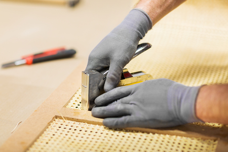 assembler with staple gun making furniture
