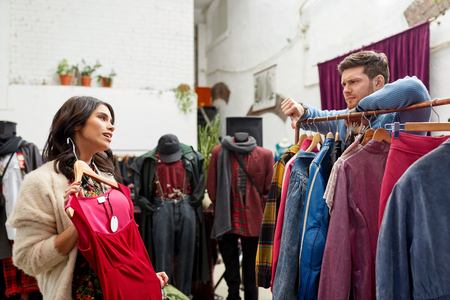 couple choosing clothes at vintage clothing store Banco de Imagens