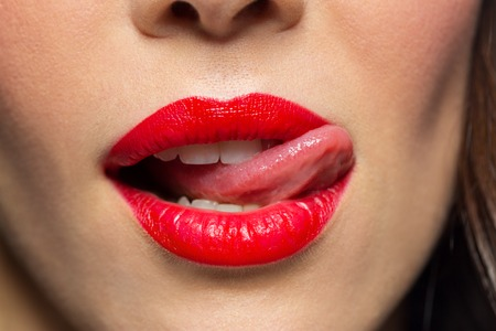 close up of woman with red lipstick licking lips Stockfoto