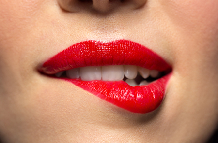 close up of woman with red lipstick biting lip