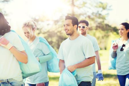 group of volunteers with garbage bags in park