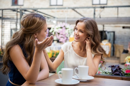 happy young women drinking coffee at outdoor cafe