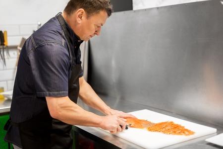 man slicing smoked salmon fish fillet