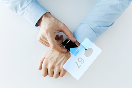 business, technology and people concept - close up of male hands wearing smart watch with social media icons