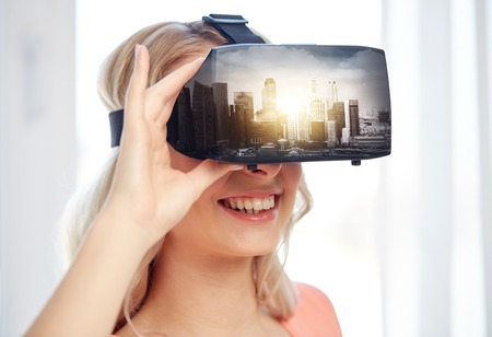 technology, augmented reality, entertainment and people concept - happy young woman with virtual headset or 3d glasses playing video game with singapore city on screen Stock Photo