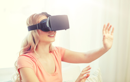 technology, virtual reality, entertainment and people concept - happy young woman with virtual reality headset or 3d glasses playing game at home and touching something invisible