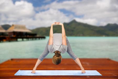 woman making yoga wide-legged forward bend outdoor Reklamní fotografie