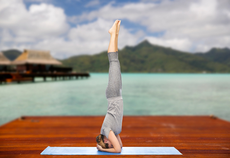 woman making yoga in headstand pose outdoors Stock Photo - 98852415