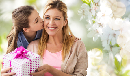 daughter kissing mother and giving her present Stock Photo