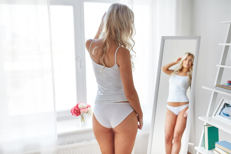 woman in underwear looking at mirror in morning Stockfoto - 98852563