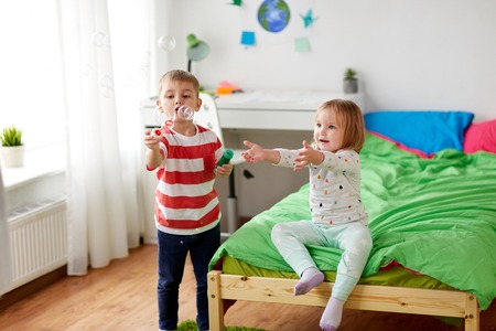 kids blowing soap bubbles and playing at home Stock Photo