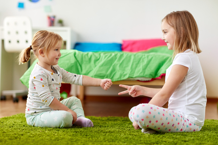 girls playing rock-paper-scissors game at home Standard-Bild - 98852647