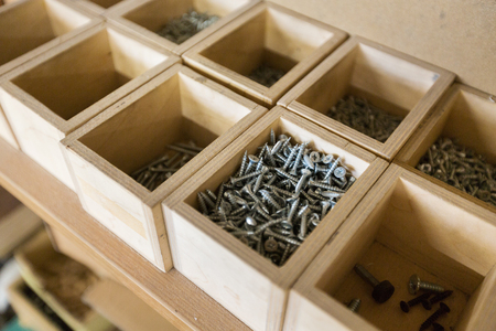 screws in wooden boxes at workshop