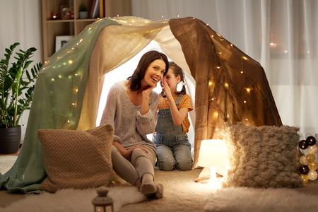 happy family whispering in kids tent at home