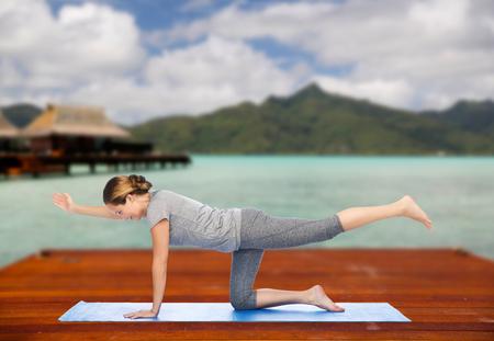 woman making yoga in balancing table pose outdoors