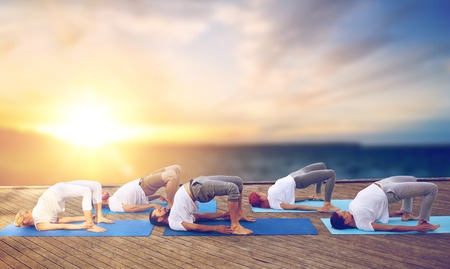 group of people doing yoga bridge pose outdoors
