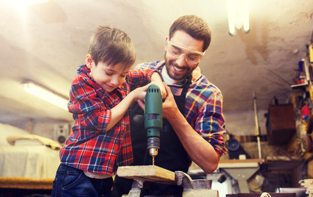 father and son with drill working at workshop Stock Photo - 98882597