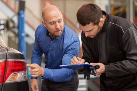 mechanic and customer looking at car taillight Stock Photo